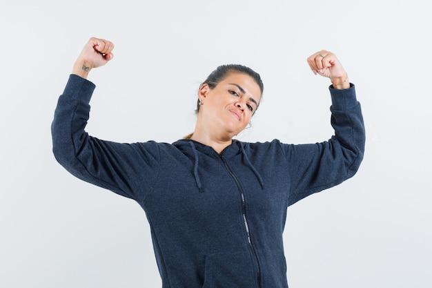 Jonge dame die haar armspieren in jasje toont en flexibel kijkt. vooraanzicht.