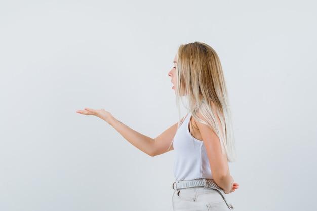 Jonge dame die haar hand met agressieve manier in witte blouse opheft en gericht kijkt.