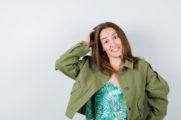Jonge dame die haar hoofd krabt terwijl ze lacht in een groene jas en besluiteloos kijkt, vooraanzicht.