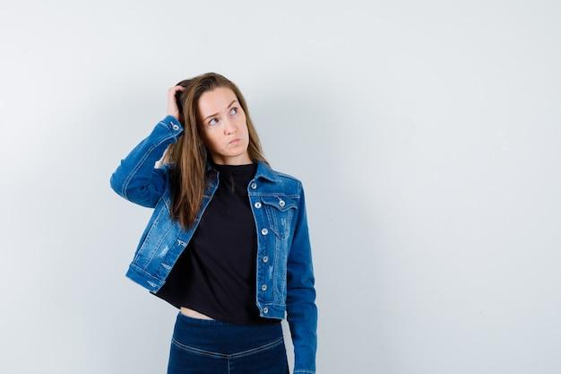 Jonge dame die haar hoofd krabt terwijl ze opkijkt in blouse, jas, spijkerbroek en peinzend kijkt.