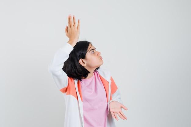 Jonge dame die haar open handpalmen in jasje, roze overhemd uitspreidt en zenuwachtig kijkt.