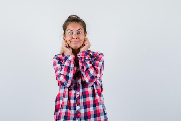 Jonge dame die haar oren in geruit overhemd naar beneden trekt en er grappig uitziet. vooraanzicht.