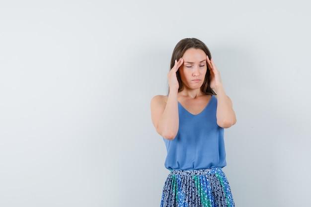 Jonge dame die haar tempels in blauwe blouse, rok masseert en moe kijkt. vooraanzicht.