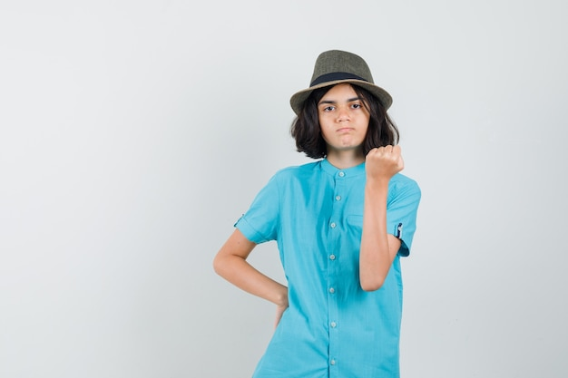 Jonge dame die haar wapenmacht in blauw overhemd, hoed toont en woedend kijkt
