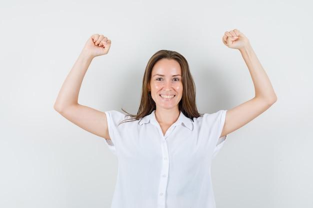 Jonge dame die haar wapens opheft terwijl zij vuisten in witte blouse toont en gelukkig kijkt.