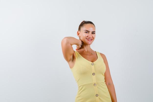 Jonge dame die hand achter hals in gele kleding houdt en vrolijk, vooraanzicht kijkt.