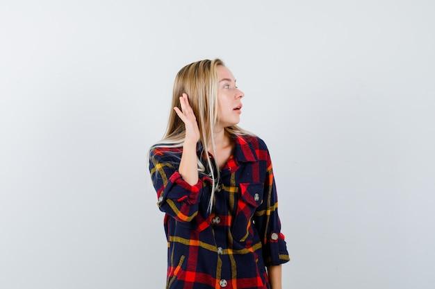 Jonge dame die hand achter het oor in geruit overhemd houdt en zich afvraagt, vooraanzicht.