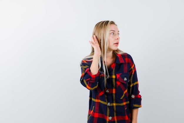 Jonge dame die hand achter oor in geruit overhemd houdt en gericht, vooraanzicht kijkt.