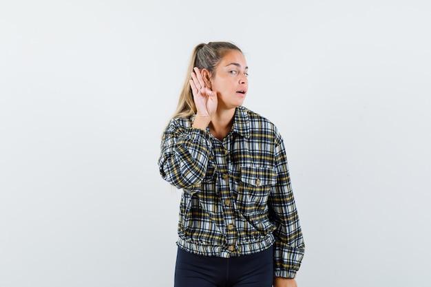 Jonge dame die hand achter oor in overhemd, korte broek houdt en nieuwsgierig, vooraanzicht kijkt.