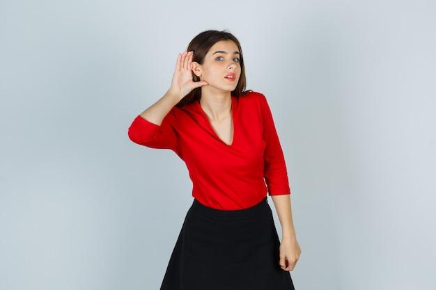 Jonge dame die hand achter oor in rode blouse, rok houdt en nieuwsgierig kijkt