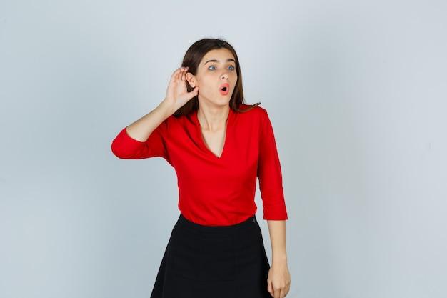 Jonge dame die hand achter oor in rode blouse, rok houdt en verbaasd kijkt