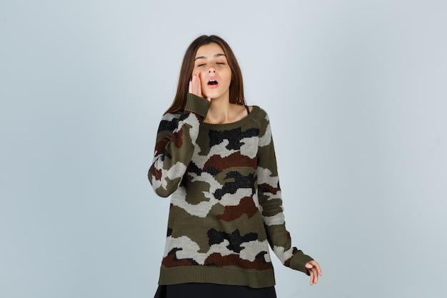 Jonge dame die hand dichtbij mond houdt om geheim in sweater te vertellen en verward kijkt
