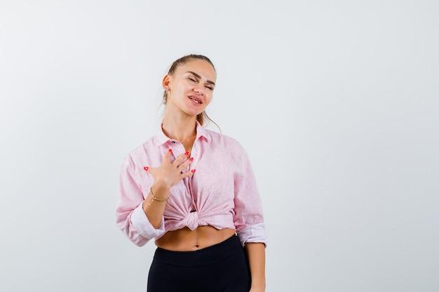 Jonge dame die hand op borst in overhemd, broek houdt en dankbaar kijkt. vooraanzicht.