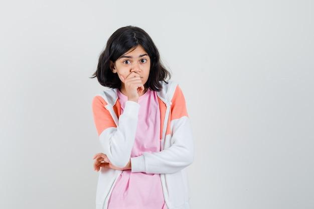Jonge dame die hand op haar mond houdt terwijl weg in jasje, roze overhemd kijkt en attent kijkt.