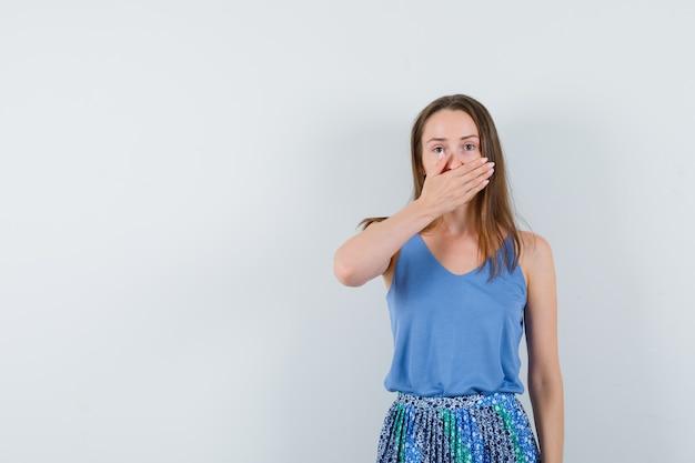 Jonge dame die hand op haar mond in blauwe blouse, rok houdt en walgt, vooraanzicht kijkt.