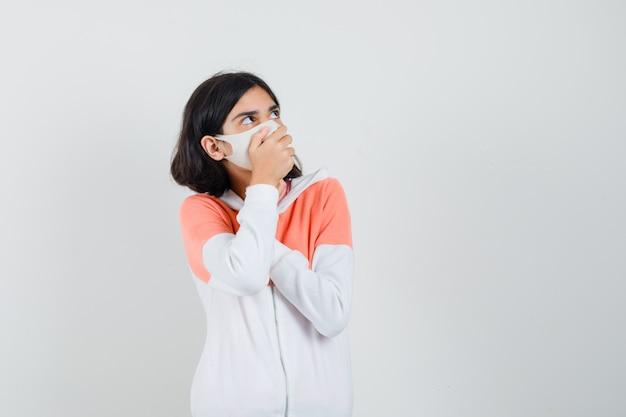 Jonge dame die hand op haar mond in hoodie, gezichtsmasker houdt en bang kijkt.