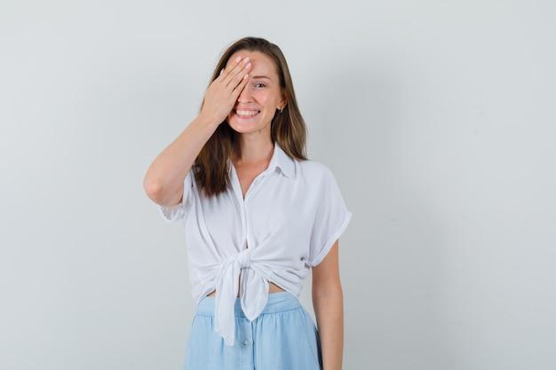 Jonge dame die hand op haar oog houdt terwijl ze in blouse, rok glimlacht en speels kijkt