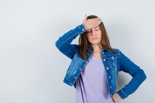 Jonge dame die hand op het voorhoofd houdt, ogen sluit in t-shirt, jas en er moe uitziet, vooraanzicht.