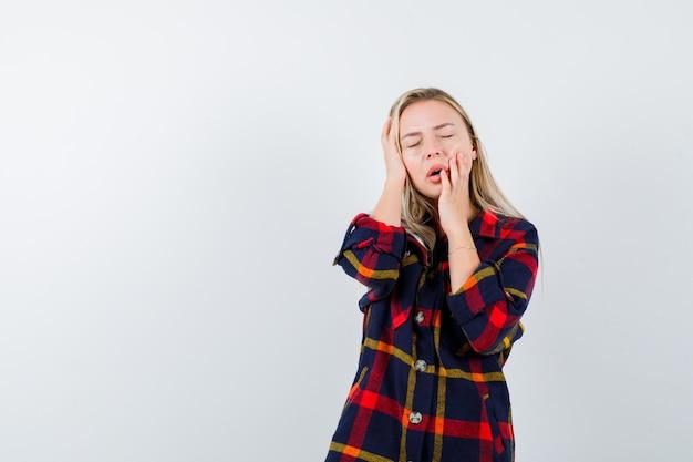Jonge dame die hand op hoofd houdt terwijl hand op wang in geruit overhemd en slaperig, vooraanzicht kijkt.