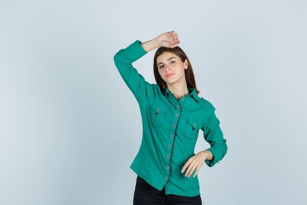 Jonge dame die hand op hoofd in groen overhemd houdt en peinzend, vooraanzicht kijkt.