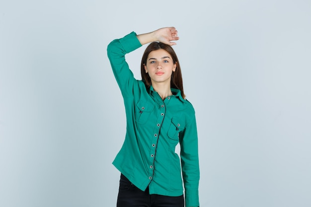 Jonge dame die hand op hoofd in groen overhemd houdt en zelfverzekerd kijkt, vooraanzicht.