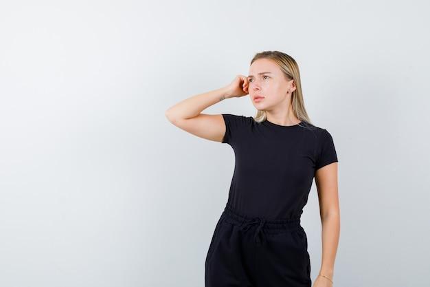 Jonge dame die hand op hoofd in t-shirt, broek houdt en nadenkend, vooraanzicht kijkt.