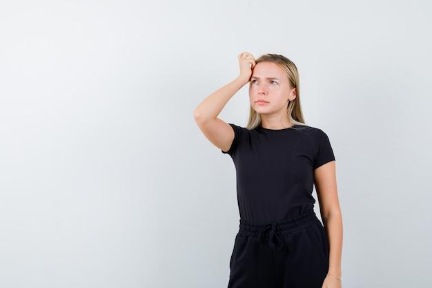 Jonge dame die hand op hoofd in t-shirt, broek houdt en peinzend, vooraanzicht kijkt.