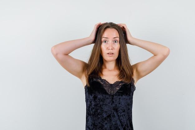 Jonge dame die hand op hoofd in zwarte blouse houdt en onrustig kijkt