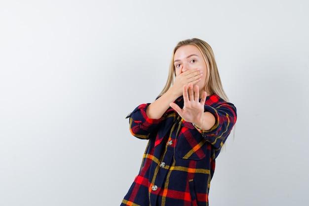 Jonge dame die hand op mond houdt terwijl stopgebaar in gecontroleerd overhemd wordt getoond en bang kijkt. vooraanzicht.