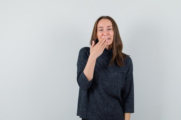 Jonge dame die hand op mond in overhemd houdt en positief kijkt