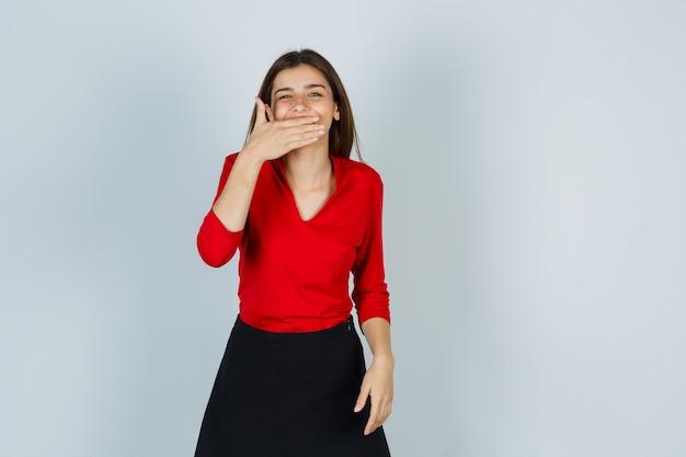 Jonge dame die hand op mond in rode blouse, rok houdt en er schattig uitziet