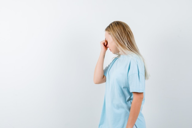 Jonge dame die hand op neus in t-shirt houdt en uitgeput, vooraanzicht kijkt.