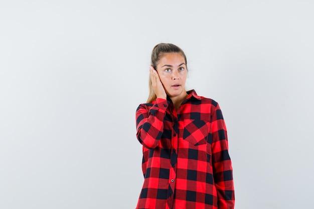 Jonge dame die hand op oor in geruit overhemd houdt en peinzend kijkt