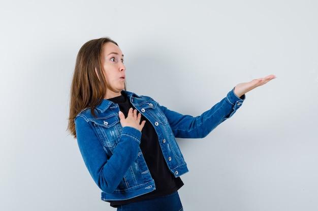Jonge dame die hand uitrekt om iets in blouse, jas te laten zien en er verbaasd uitziet. vooraanzicht.