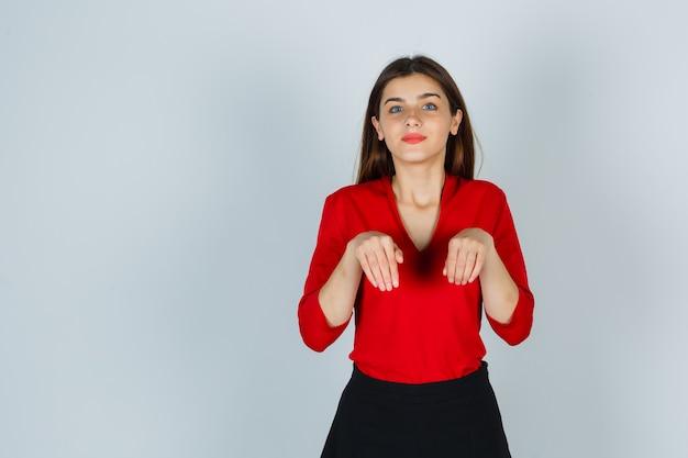 Jonge dame die handen houdt als poten in rode blouse, rok en er schattig uitziet