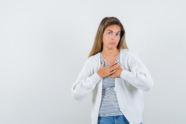 Jonge dame die handen op borst in t-shirt, jasje houdt en verbaasd, vooraanzicht kijkt.