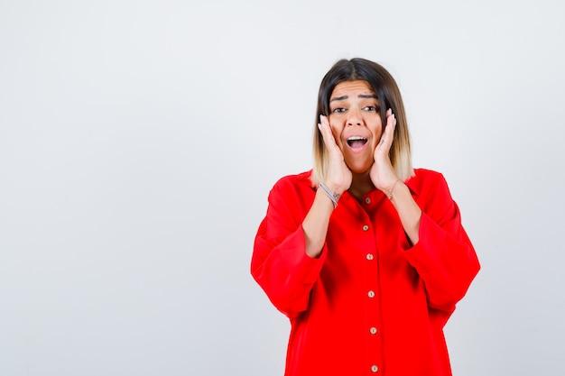 Jonge dame die handen op de wangen houdt in een rood oversized shirt en er opgewonden uitziet, vooraanzicht.