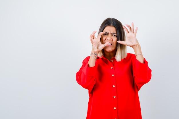 Jonge dame die handen op een agressieve manier houdt in een rood oversized shirt en er geïrriteerd uitziet. vooraanzicht.