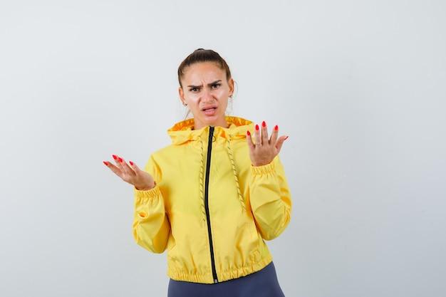 Jonge dame die handen uitrekt in een vragend gebaar in gele jas en er serieus uitziet, vooraanzicht.
