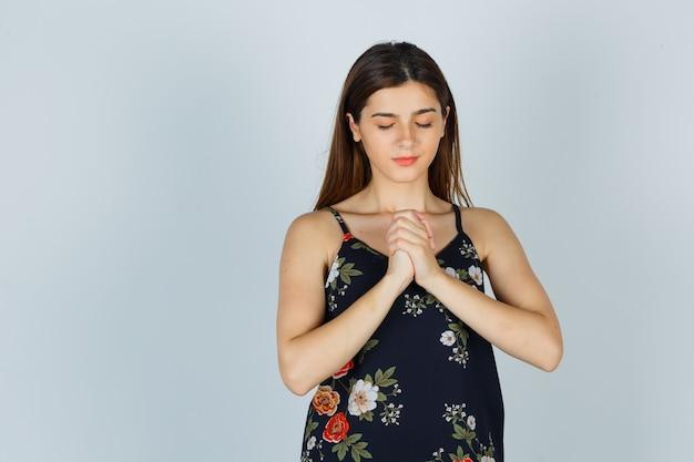 Jonge dame die handen vasthoudt in een biddend gebaar in blouse en er hoopvol uitziet, vooraanzicht.