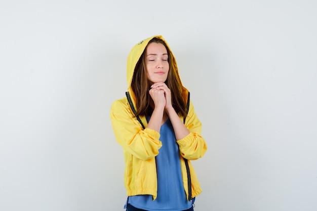 Jonge dame die handen vasthoudt in een biddend gebaar in t-shirt, jas en er hoopvol uitziet. vooraanzicht.