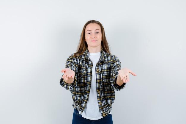 Jonge dame die handpalm uitspreidt in t-shirt, jasje, spijkerbroek en op zoek hulpeloos, vooraanzicht.