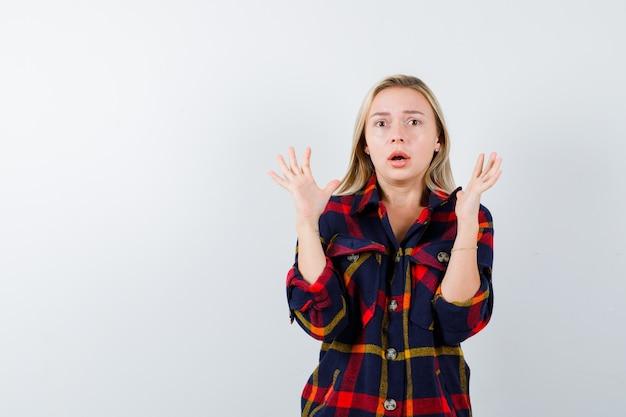 Jonge dame die handpalmen in overgave gebaar in geruit overhemd toont en bang, vooraanzicht kijkt.