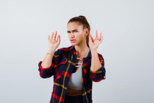 Jonge dame die handpalmen toont in overgavegebaar in top, geruit hemd en er serieus uitziet. vooraanzicht.