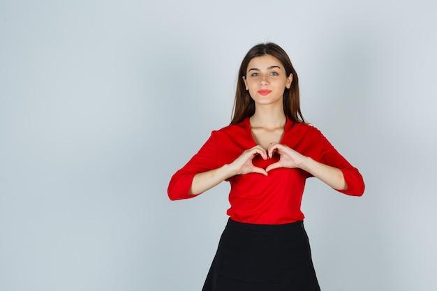 Jonge dame die hartgebaar in rode blouse, rok toont en prachtig kijkt