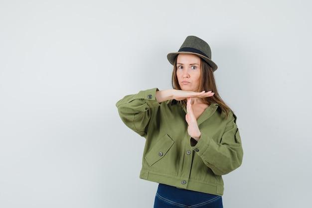 Jonge dame die het gebaar van de tijdonderbreking in de hoed van de jasbroeken toont en ernstig kijkt