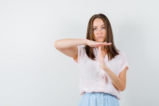 Jonge dame die het gebaar van de tijdpauze in t-shirt, rok toont en ernstig, vooraanzicht kijkt.