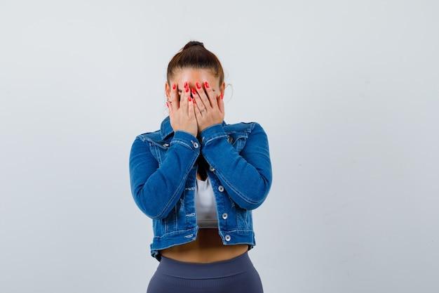 Jonge dame die het gezicht bedekt met de handen in de bovenkant, een spijkerjasje en er bedroefd uitziet. vooraanzicht.