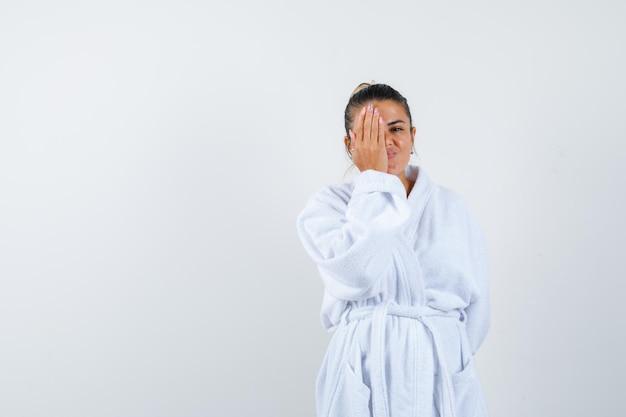 Jonge dame die het oog bedekt met de hand in een badjas en er zelfverzekerd uitziet