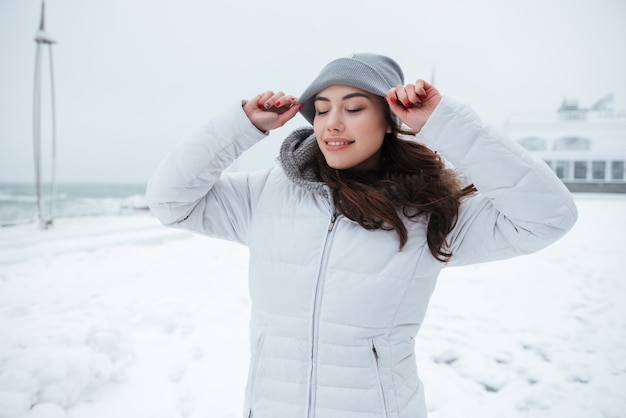 Jonge dame die hoed draagt die bij koude de winterdag loopt